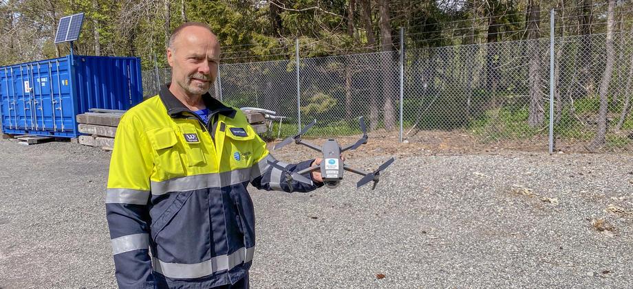 Mann i arbeidsklær viser frem drone.